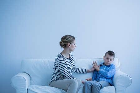 Foto de Serious mother and her autistic son sitting on a sofa - Imagen libre de derechos