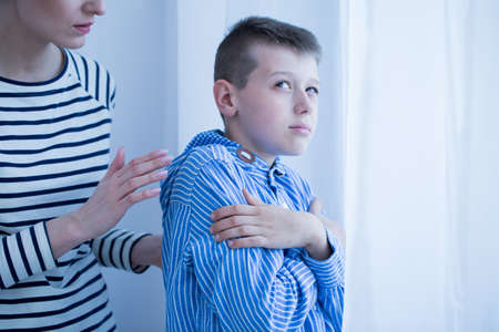 Foto de Serious mother talking to her autistic son - Imagen libre de derechos