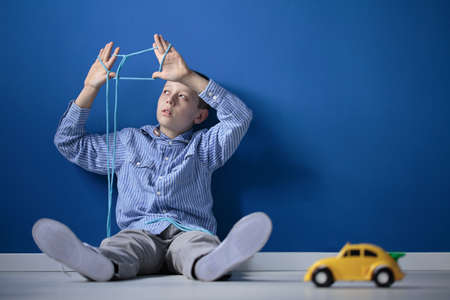 Foto de Boy sitting on a floor and playing with a rope and toy car - Imagen libre de derechos