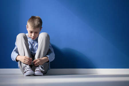 Foto de Depressed boy sitting on a floor in blue room - Imagen libre de derechos