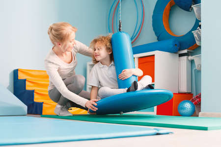 Photo for Boy using sensory integration equipment and a woman helping him - Royalty Free Image