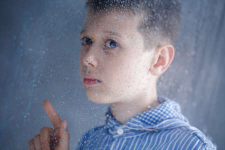 Foto de Sad boy behind the window on a rainy day - Imagen libre de derechos