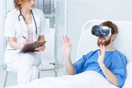 Foto de Young male patient in VR talking to young female doctor - Imagen libre de derechos
