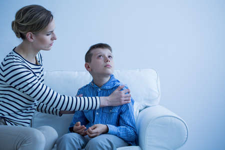 Foto de Mother and her autistic son sitting on the sofa - Imagen libre de derechos
