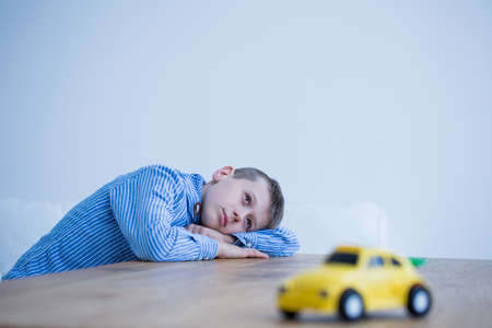 Foto de Thoughtful little boy and toy car on a table - Imagen libre de derechos