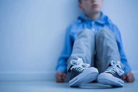 Foto de Sad boy sitting on a floor in a room - Imagen libre de derechos