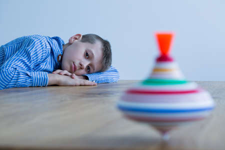 Foto de Sad boy and spinning top on wooden table - Imagen libre de derechos