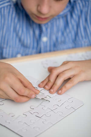 Foto de Focused boy solving a puzzle on a table - Imagen libre de derechos