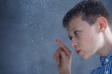 Foto de Sad boy looking at raindrops on the window - Imagen libre de derechos