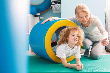 Foto de Professional therapist explaining new exercise to a little boy - Imagen libre de derechos