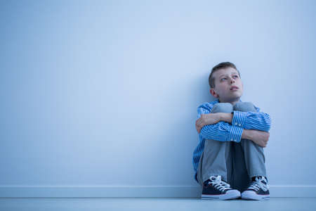 Foto de Lonely autistic child sitting on a floor in a room - Imagen libre de derechos