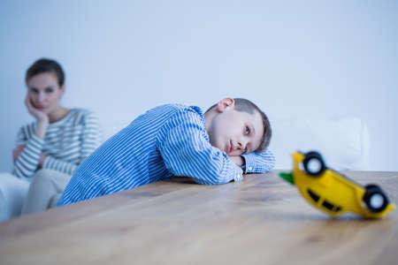 Foto de Depressed boy and his sad mom in a room with wooden table - Imagen libre de derechos
