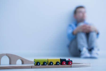 Foto de Toy train in a room and sad boy sitting on the floor - Imagen libre de derechos