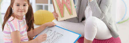 Foto de Girl learning letters with school counsellor on additional classes - Imagen libre de derechos