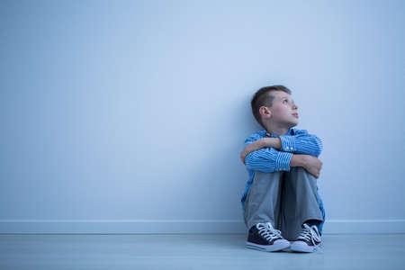 Foto de Sad lonely child sitting on a floor in an empty room - Imagen libre de derechos