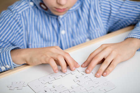 Photo pour Focused little boy solving a white puzzle - image libre de droit