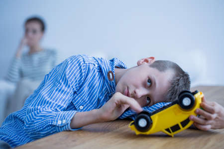 Foto de Sad autistic boy playing with toy car on wooden table - Imagen libre de derechos
