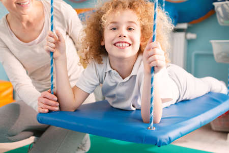 Photo for Happy little boy laying on therapy swing - Royalty Free Image