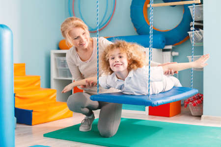Foto de Woman helping a smiling boy to exercise on a therapy swing - Imagen libre de derechos