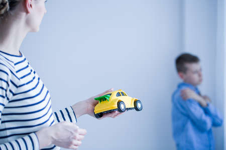 Foto de Mom giving toy car to her sad son standing in a room - Imagen libre de derechos