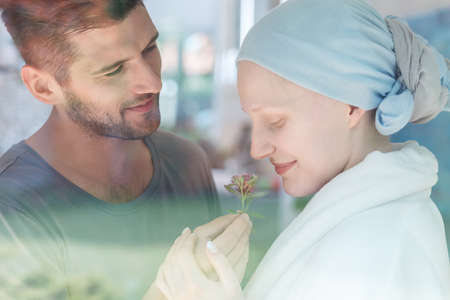 Foto de Young sick woman smelling a fresh flower from her husband - Imagen libre de derechos