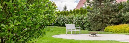 Foto de Panorama of well-kept home garden with a white bench and a small table - Imagen libre de derechos