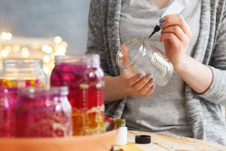 Photo for Young woman decorating DIY jars with paint - Royalty Free Image