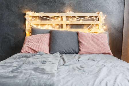Photo pour Cozy dreamy bed with decorated DIY pallet headboard - image libre de droit
