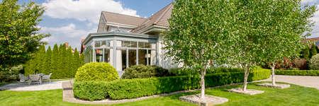 Foto de House exterior with elegant orangery in well-kept and green garden with a terrace and trees - Imagen libre de derechos
