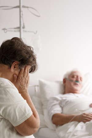 Photo pour Senior woman crying next to her sick husband's hospital bed - image libre de droit