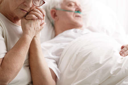 Photo pour Dying senior man in hospital bed and his sad wife holding his hand - image libre de droit