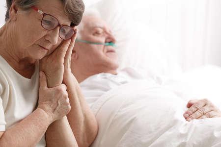 Photo pour Sad senior woman holding his sick husband's hand - image libre de droit