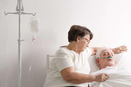 Foto de Senior woman taking care of her sick husband in hospice - Imagen libre de derechos