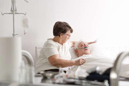Photo pour Senior woman taking care of her sick husband in hospital - image libre de droit