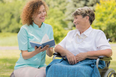 Foto de Young nurse sitting close to the elderly woman on a wheelchair and reading her a book in a garden - Imagen libre de derechos
