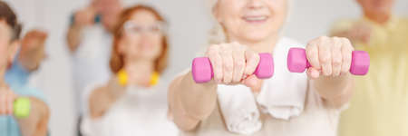 Photo pour Active senior woman training with dumbbells in gym - image libre de droit