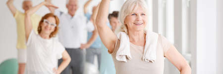 Photo pour Energetic smiling senior woman exercising with a group of elders - image libre de droit
