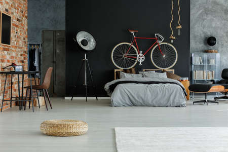 Photo pour Stylish designed spacious bedroom with red bike above the bed - image libre de droit