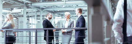 Foto per Businesswoman talking with two, elegant investors, panorama - Immagine Royalty Free