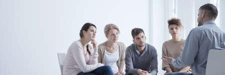 Foto de Support group sitting in circle while man confiding his problems - Imagen libre de derechos