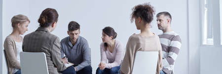 Foto de Meeting of support group talking about problems sitting in circle - Imagen libre de derechos