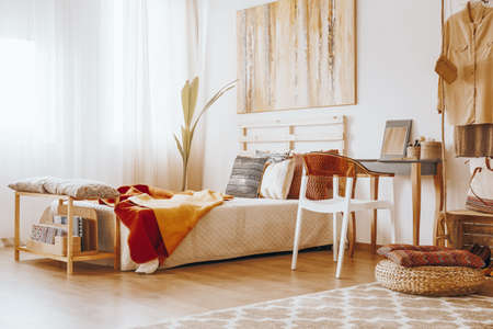 Photo pour Wooden bed with blanket and pillows standing in cozy bedroom in sandy colors - image libre de droit
