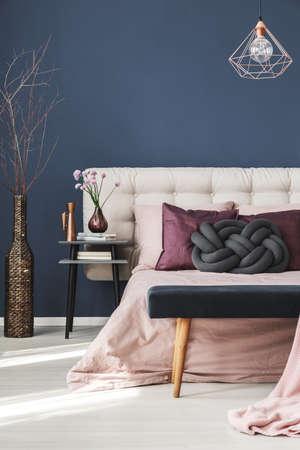 Photo pour Thin twigs in decorative wicker vase standing in the corner of bedroom - image libre de droit
