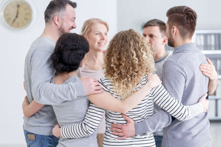Foto de People having group hug during therapy in rehab - Imagen libre de derechos