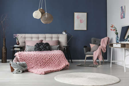 Photo pour Dark grey comfy armchair with cushion and pink blanket in the corner of the room - image libre de droit