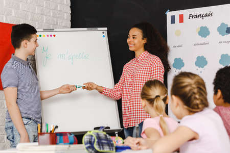 Photo for Young boy by the white board during french classes - Royalty Free Image