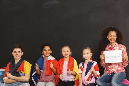 Photo for Young kids different flags sitting next to teacher - Royalty Free Image