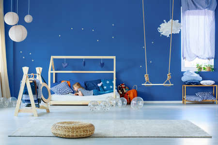 Foto de Young girl reading book in stylish scandinavian decorated bedroom - Imagen libre de derechos