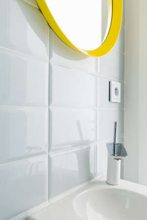 Photo pour Rectangular white tiles in a modern bathroom, with a mirror in a yellow frame and a ceramic sink - image libre de droit