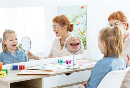 Foto de Speech therapist using fun mirror exercises during session with child - Imagen libre de derechos